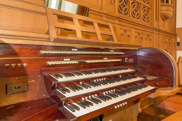 A big piano with keys made of red wood