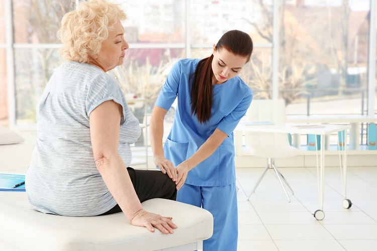 Senior woman seeking knee pain relief with physical therapy and exercise