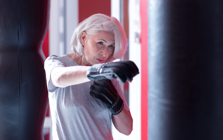 Senior woman boxing a punching bag.