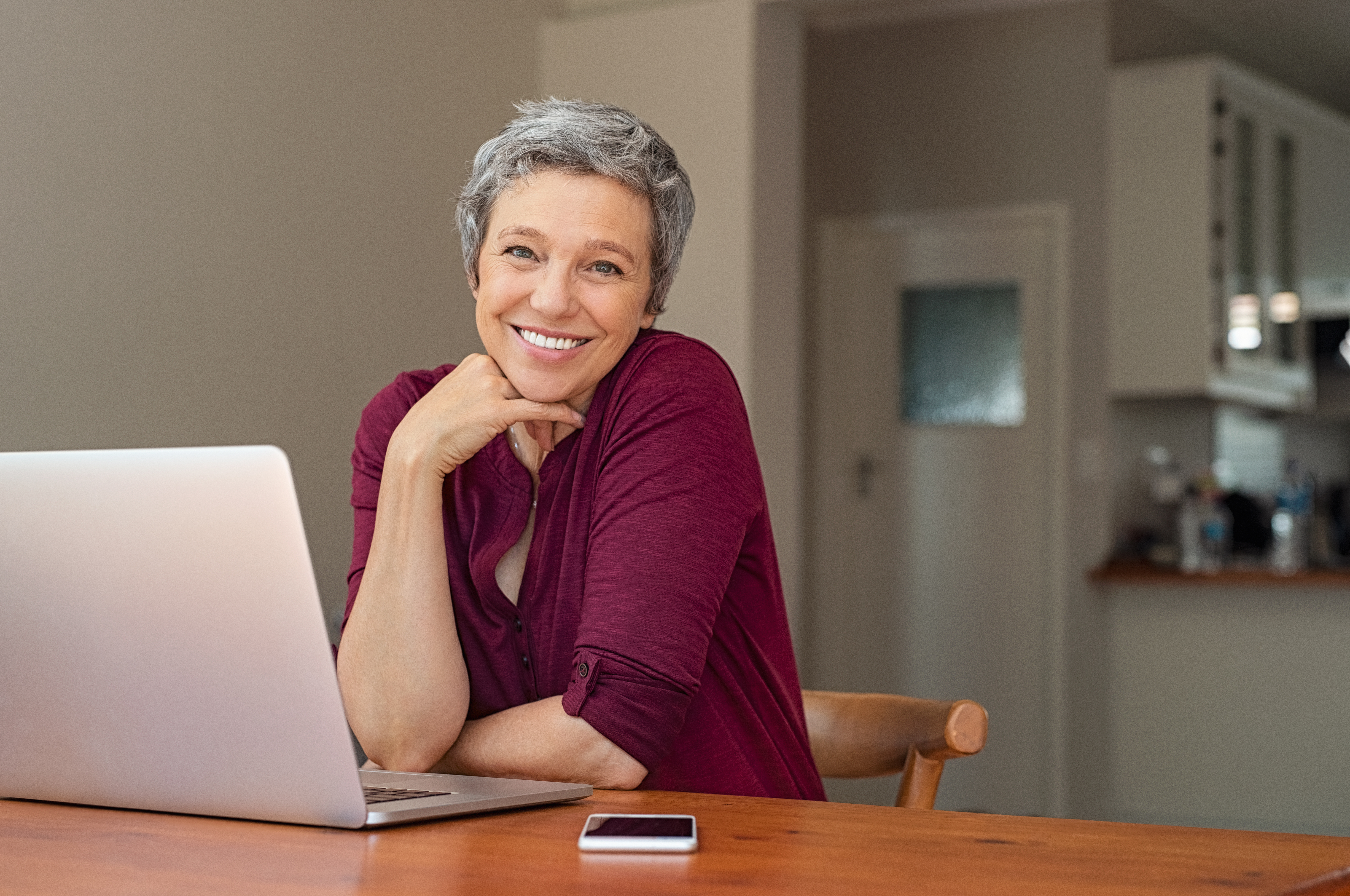 Older adult women using a laptop with their mobile phone in reach