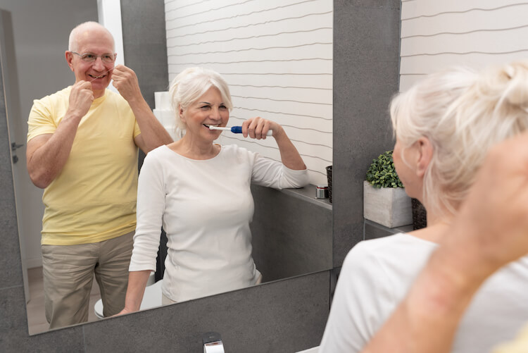 A senior couple practicing good oral hygiene by brushing and flossing together.