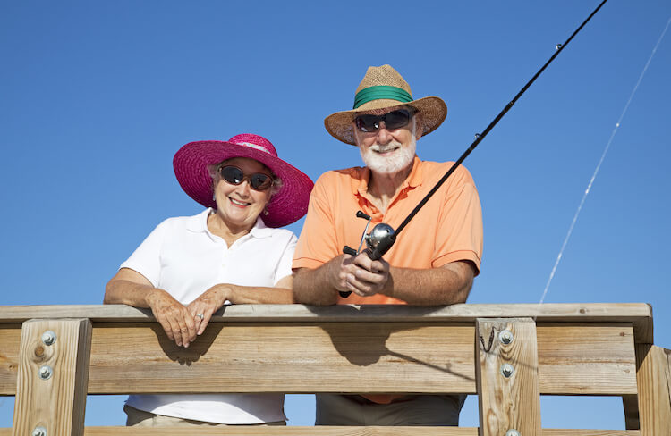 Senior couple protects themselves from the sun while fishing, using hats and sunglasses.