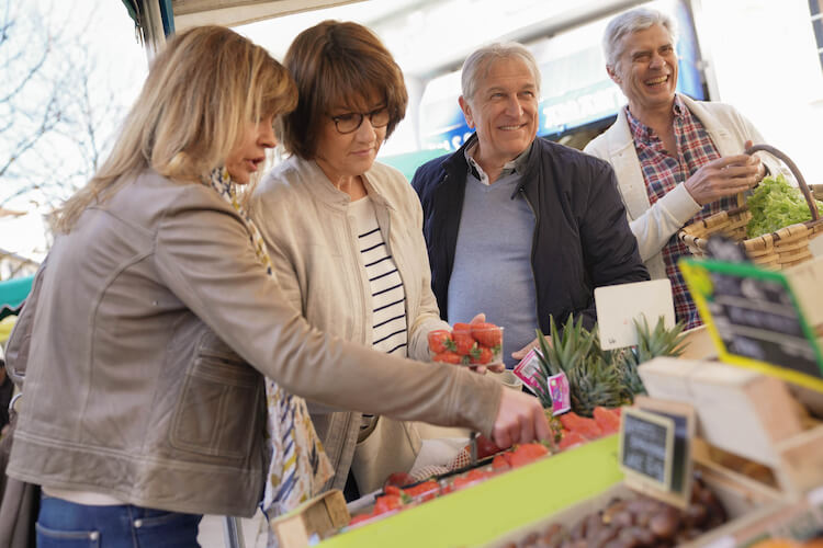 Seniors at the farmer's market buying fruits and vegetables.