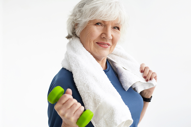 Active senior female holding a lightweight dumbbell with a white towel over her shoulders