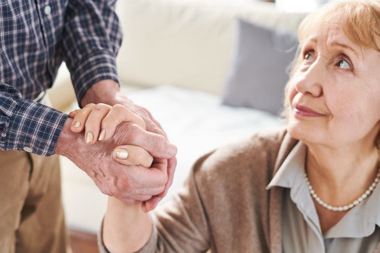 Senior woman looks at her caregiver spouse as he tends to her care.