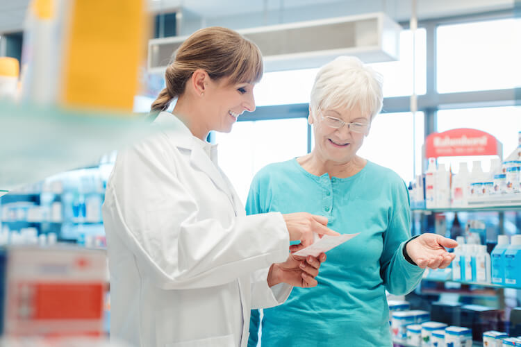 Senior woman speaks with pharmacist about medication fall risk.
