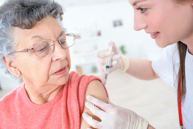 A senior woman receives her yearly flu shot.