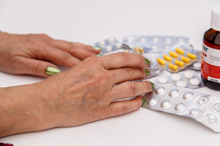 The hands of a senior woman holding nutritional supplements.