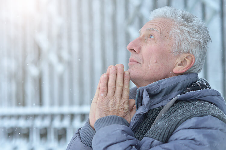 A senior man sits outside in the snow.