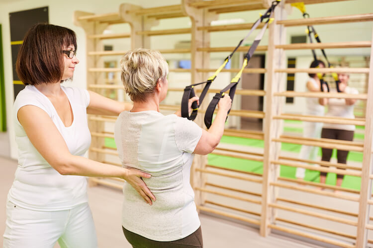 A senior personal trainer works with a woman doing sling exercises.