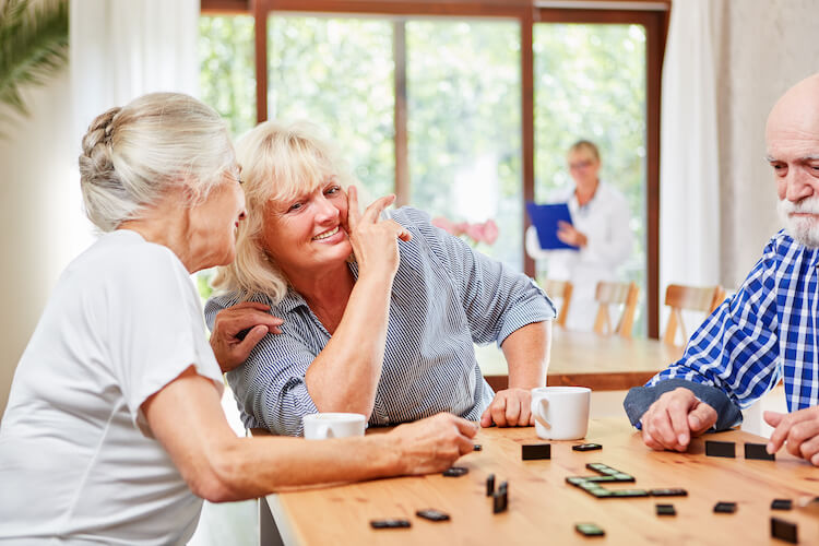 Seniors enjoy a game of dominoes at a retirement community