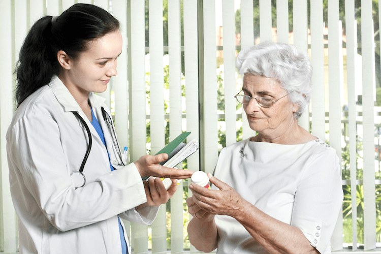 A senior woman discusses medications and cognitive screenings with her doctor.