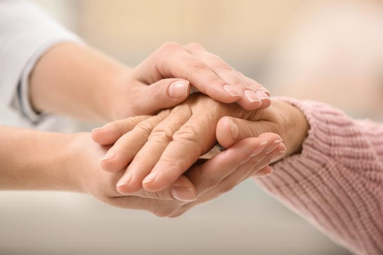Nurse Holding Hands Of Elderly Woman