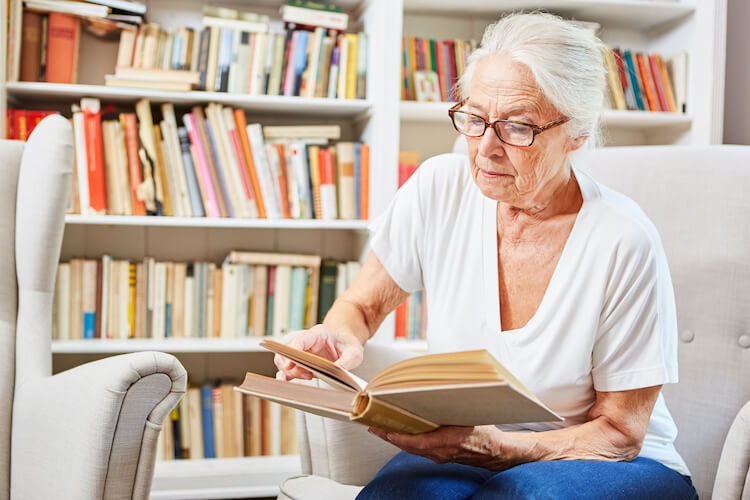 Senior woman reading a book to improve her memory and keep her brain sharp.