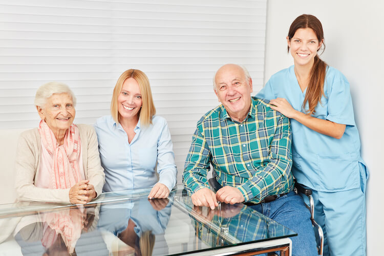 A happy adult child with her aging parents and nurse at a senior living community.