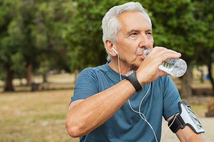 A senior man drinking water in a park after going for a jog.