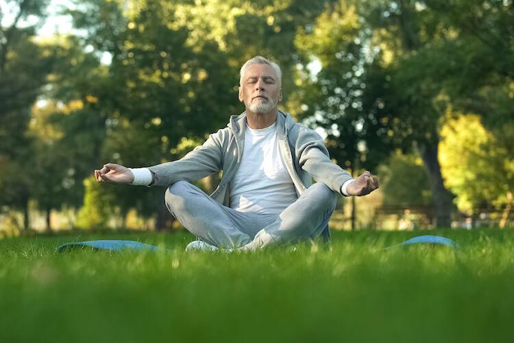 A senior man meditating in a park.