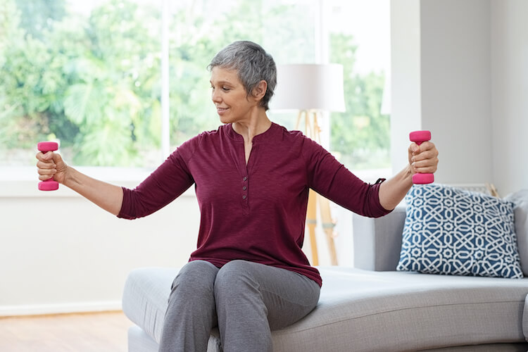 Senior woman lifting weights and working out at home.