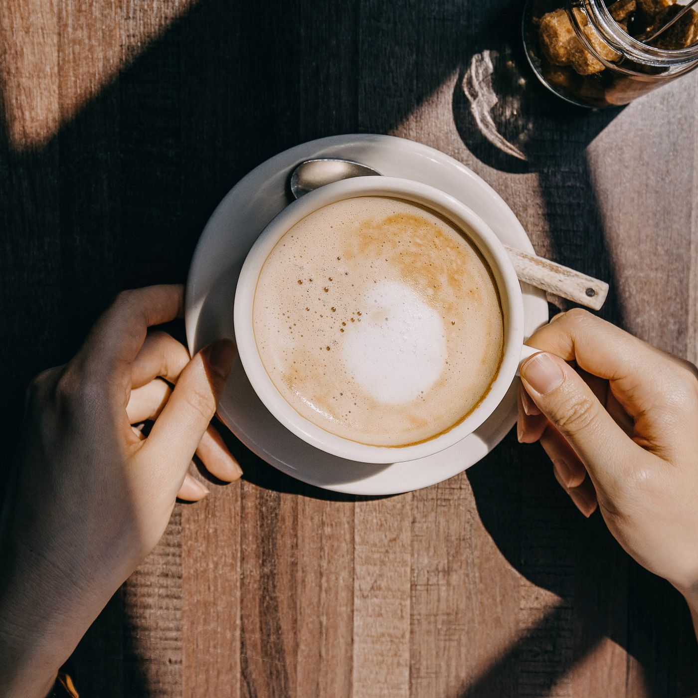Person touching a white coffee cup and saucer filled with a cappuccino