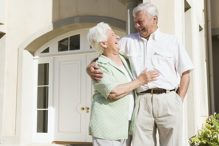 Happy senior couple standing in an independent living community.