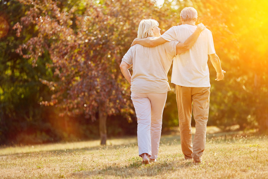 Two seniors go for a walk together outdoors.