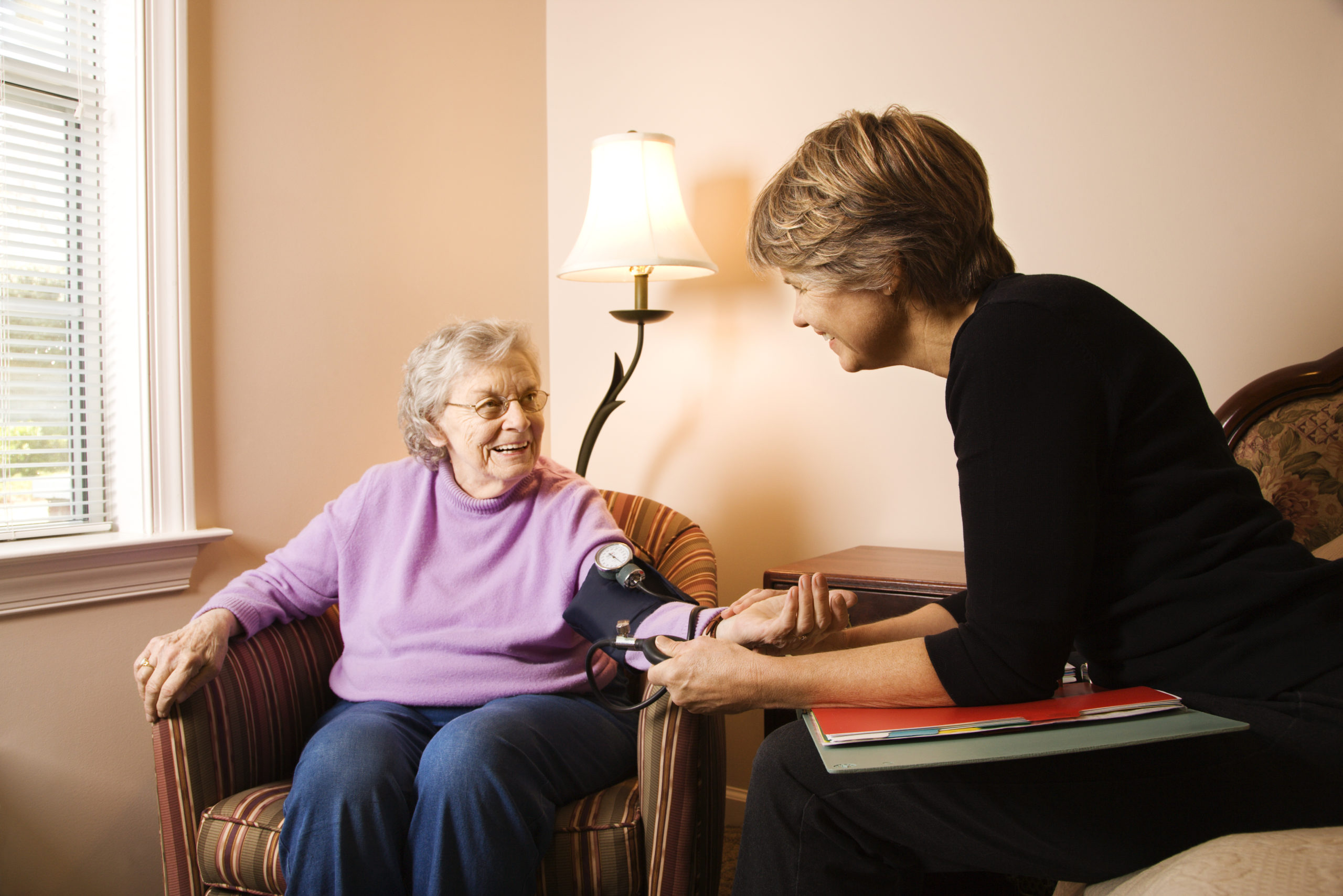 Happy senior woman gets her blood pressure taken in assisted living.