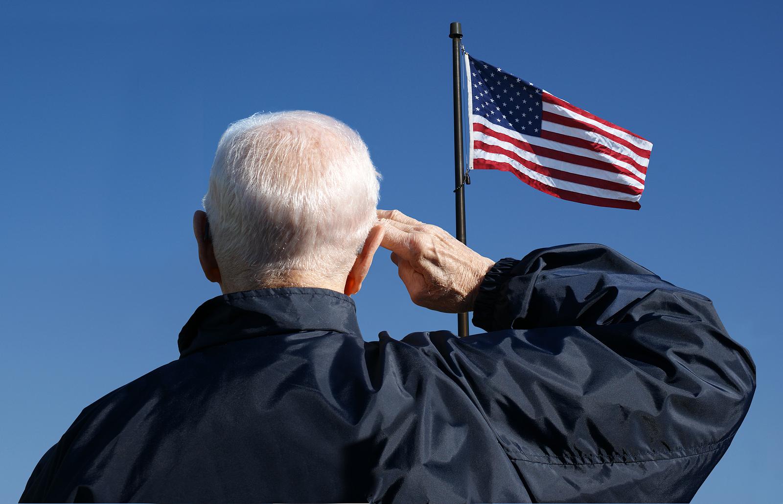 Senior man salutes American flag.