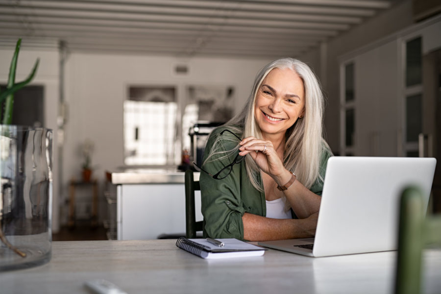 Happy senior woman sitting with her laptop at home.