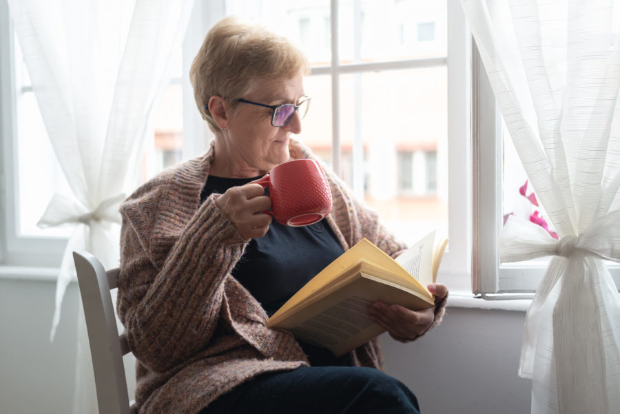 Happy senior woman reads a book indoors.